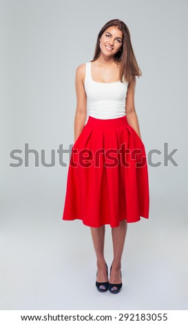 Full length portrait of attractive smiling woman in skirt posing over gray background and looking at camera - stock photo