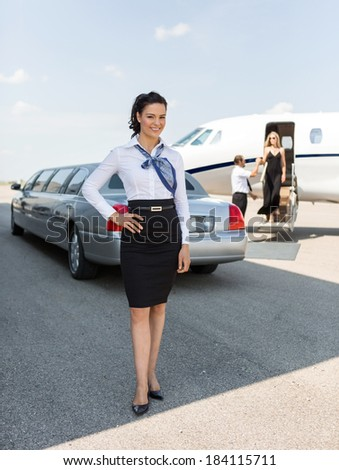 Full length portrait of attractive stewardess standing against limousine and private jet at airport terminal - stock photo