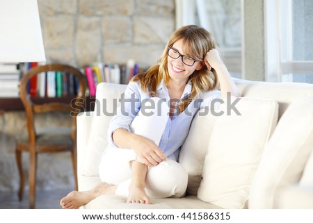 Full length portrait of attractive woman relaxing on sofa in her luxury home.