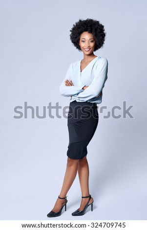 Full length portrait  of attractive young black african model wears smart business attire in studio and smiling - stock photo