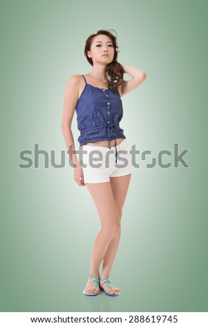 Full length portrait of attractive young pretty asian woman posing to the camera. Isolated on the white background. - stock photo