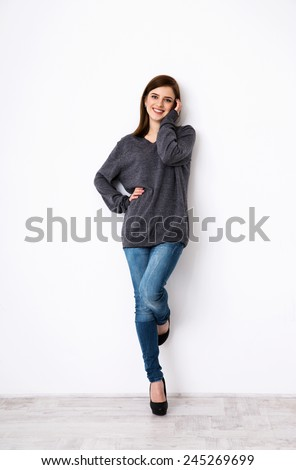 Full length portrait of attractive young woman leaning on the wall - stock photo