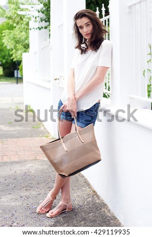 Full length portrait of attractive young woman on sidewalk with purse - stock photo
