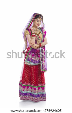Full length portrait of beautiful bride standing against white background - stock photo