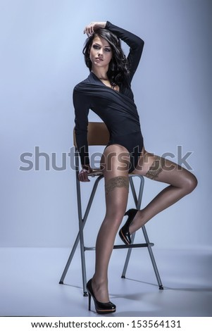 Full-length portrait of beautiful brunette young woman sitting in fashionable body and black shoes - stock photo