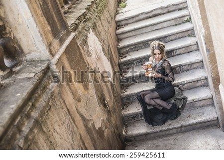 Full length Portrait of Beautiful caucasian woman sit on concrete old retro abandoned ladder along fence in perspective Cute girl hold black tea cup and dream about sweet life Wear sexy long dress  - stock photo