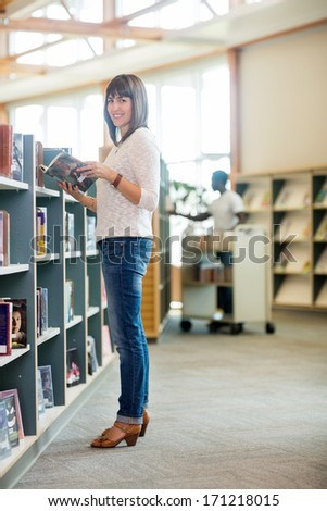 Full length portrait of beautiful college student holding book in bookstore - stock photo