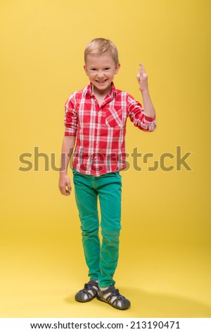 Full-length portrait of beautiful funny smiling little boy wearing red checked shirt and green paints showing that he is cool. Isolated on yellow background - stock photo