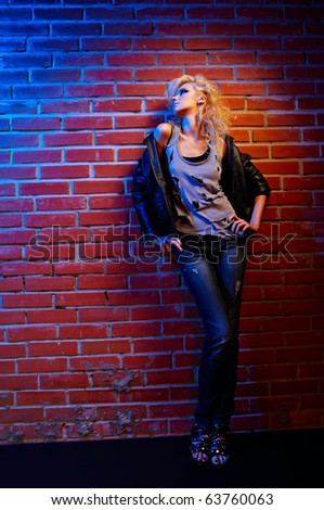 full-length portrait of beautiful glam rock style blonde girl standing near red brick wall - stock photo