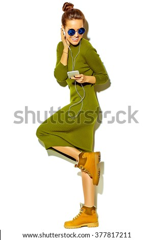 Full length portrait of beautiful happy cute smiling brunette woman girl in casual green hipster summer clothes with no makeup isolated on white listening music in smartphone with headphones - stock photo