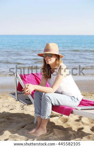 Full length portrait of beautiful mature woman relaxing on the sandy beach while sitting on the sunbed.