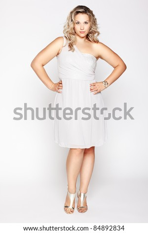 full-length portrait of beautiful plus size curly young blond woman posing on gray in white dress and court shoes - stock photo