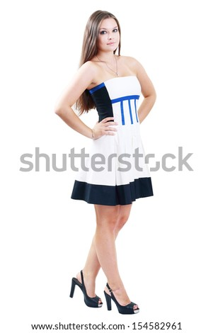 full-length portrait of beautiful plus size curly young brunette woman posing on gray in white dress and court shoes - stock photo