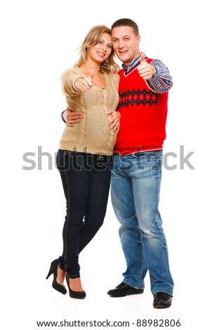 Full length portrait of beautiful pregnant woman with husband showing thumbs up isolated on white - stock photo
