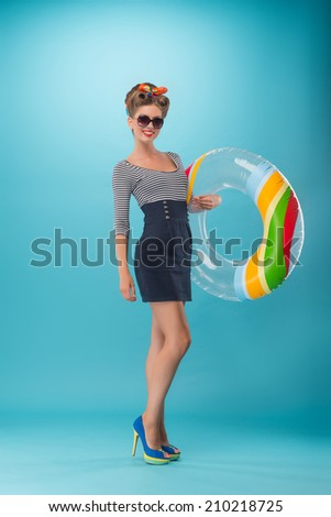 Full length portrait of beautiful sexy girl with pretty smile in pinup style wearing navy color dress holding inflatable ring isolated on blue - stock photo