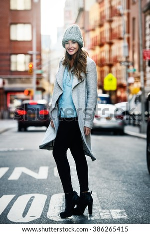 Full length portrait of beautiful smiling woman walking on city street - stock photo