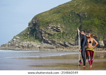 Full length portrait of beautiful surf couple of blond model and brunette man posing on the beach standing against big mountain rock in lagoon - stock photo
