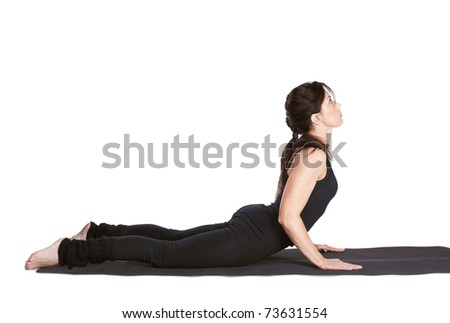 full-length portrait of beautiful woman working out yoga excercise bhujangasana (cobra pose) on fitness mat