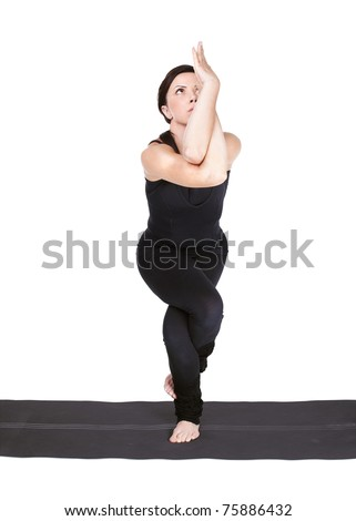 full-length portrait of beautiful woman working out yoga excercise garudasana (eagle pose) on fitness mat - stock photo