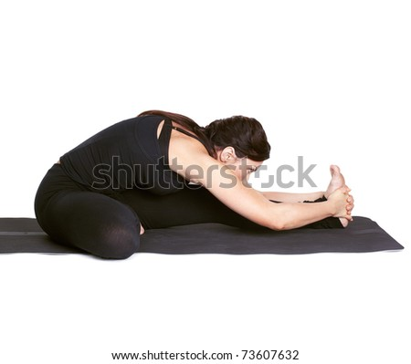 full-length portrait of beautiful woman working out yoga excercises Janu shirshasana on fitness mat - stock photo