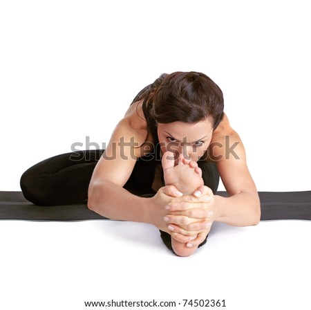 full-length portrait of beautiful woman working out yoga excercises Janu shirshasana pose on fitness mat - stock photo