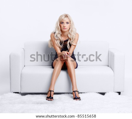 full-length portrait of beautiful young blond woman on couch with white furs on floor - stock photo