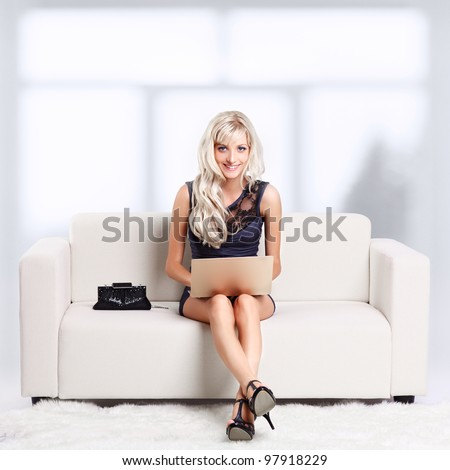 full-length portrait of beautiful young blond woman relaxing on couch with laptop