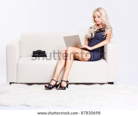 full-length portrait of beautiful young blond woman sitting on couch with laptop on her knees