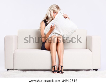 full-length portrait of beautiful young blond woman sitting on couch with remote control watching scary movie and hiding behind the pillow