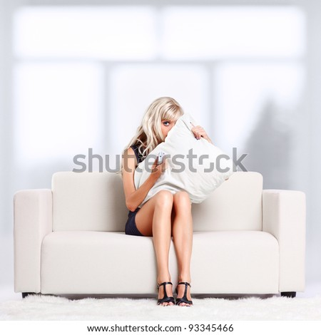 full-length portrait of beautiful young blond woman sitting on couch with remote control watching scary movie and hiding behind the pillow - stock photo