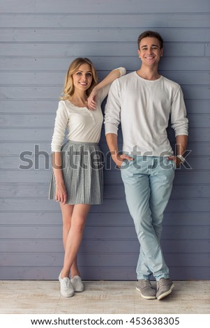 Full length portrait of beautiful young couple in casual clothes looking at camera and smiling, standing against gray wall - stock photo