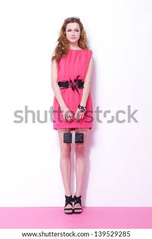 Full length Portrait of beautiful young woman with her handbag posing - stock photo
