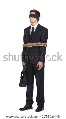Full-length portrait of blind-folded businessman tied with the rope, isolated on white. Concept of slavery and violence - stock photo
