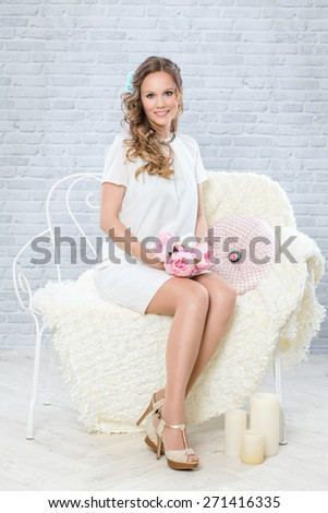Full length portrait of blond bride with wedding make-up and hairstyle, bouquet of peonies and white dress. Studio shot.