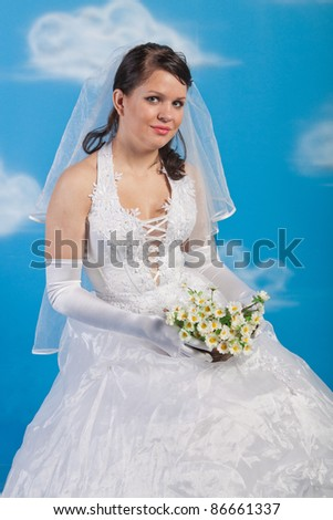 Full-length portrait of bride with bunch of camomiles - stock photo