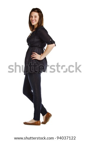 Full length portrait of brunette standing on white background with hand on hip - stock photo