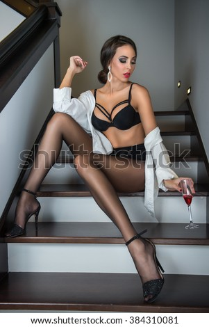 Full-length portrait of brunette woman wearing a white male shirt over black lingerie posing provocatively on steps in a modern interior. Beautiful female sitting on stairs holding a glass of wine