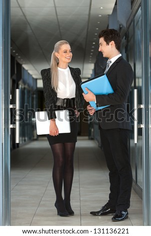 Full length portrait of business couple with file and laptop. - stock photo