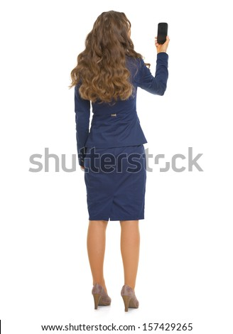 Full length portrait of business woman taking photo with cell phone . rear view - stock photo