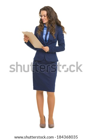 Full length portrait of business woman with clipboard - stock photo