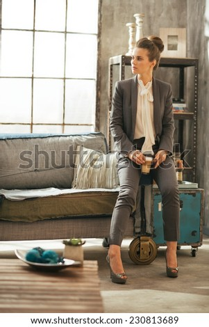 Full length portrait of business woman with coffee latte in loft apartment