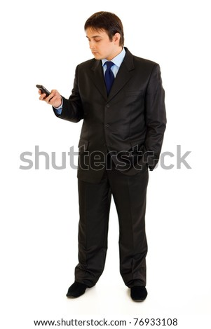 Full length portrait of businessman holding mobile in hand and looking on it isolated on white - stock photo