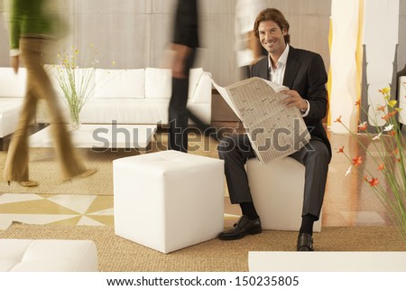 Full length portrait of businessman holding newspaper while coworkers walking in office - stock photo
