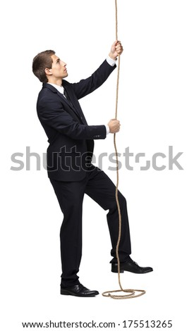 Full-length portrait of businessman swarming up the rope, isolated on white. Concept of job promotion and hard work