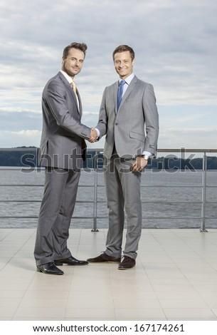 Full length portrait of businessmen shaking hands on terrace - stock photo