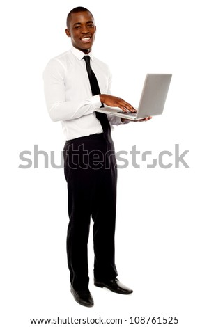 Full length portrait of businessperson holding laptop and using - stock photo