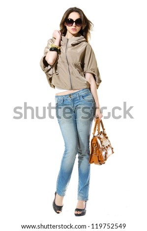 full-length portrait of casual fashion woman in sunglasses holding bag posing in studio - stock photo