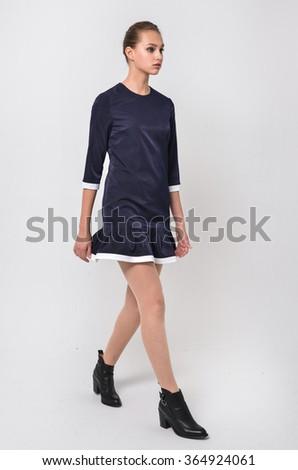 full-length portrait of casual fashion woman walking in studio   - stock photo