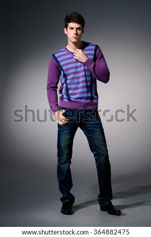 full length portrait of casual young man on light background - stock photo