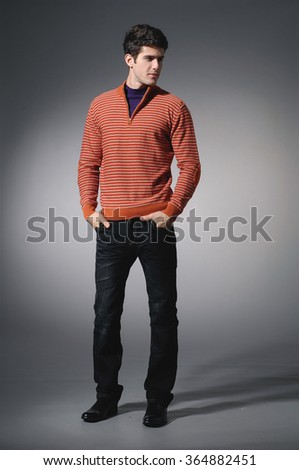 full length portrait of casual young man standing on light background - stock photo